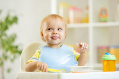 Smiling baby kid boy eating itself with spoon. Smiling cute baby kid boy eating itself with spoon stock photography
