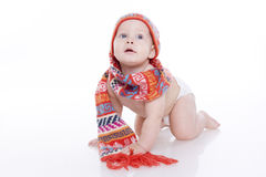 Smiling baby in knitted hat and scarf. Smiling baby in knitted hat, scarf and diaper sitting on the floor. On a white background with reflection Royalty Free Stock Images