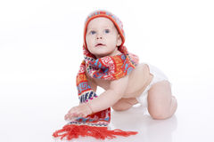Smiling baby in knitted hat and scarf. Smiling baby in knitted hat, scarf and diaper sitting on the floor. On a white background with reflection Stock Photography