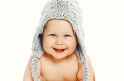 Smiling baby in knitted hat. Sitting on a white background stock image