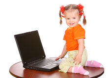 Smiling baby with laptop on table. Royalty Free Stock Image