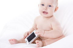 Smiling baby is learning to deal with a phone. Smiling baby baby is learning to deal with a phone. On a white background Stock Photo