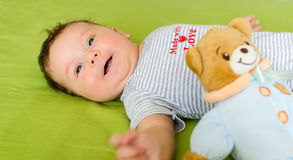 Smiling baby lies on bed with toy Stock Photo