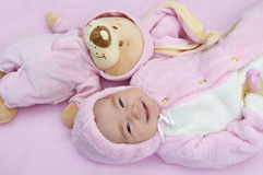 Smiling baby lies with toy bear. In pink costumes Royalty Free Stock Images