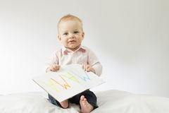 Smiling baby looking at camera. Cute infant kid holding sign Mama on big postcard.  Royalty Free Stock Images