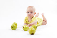 Smiling baby lying on the background to include apples Stock Image