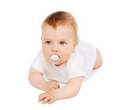 Smiling baby lying on floor with dummy in mouth Stock Photos