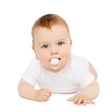 Smiling baby lying on floor with dummy in mouth Stock Images