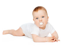 Smiling baby lying on floor with dummy in mouth Royalty Free Stock Image