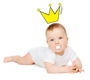 Smiling baby lying on floor with dummy in mouth Stock Photo
