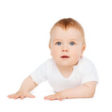 Smiling baby lying on floor and looking up Stock Images