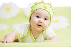 Smiling baby lying on green Stock Images