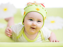 Smiling baby lying on green Stock Image
