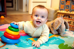 Smiling baby lying on his tummy and playing with pyramid Royalty Free Stock Photos