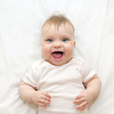 Smiling baby lying on a white bed. Royalty Free Stock Images