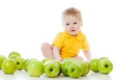 Smiling baby with many green apples. Smiling baby boy with many green apples royalty free stock photo