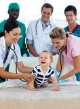 Smiling baby with a medical team in hospital Royalty Free Stock Image