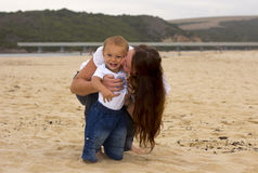 Smiling baby with mother on beach Stock Photo