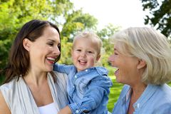 Smiling baby with mother and grandmother. Close up portrait of a smiling baby with mother and grandmother royalty free stock photography