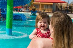 Smiling baby and mother in water park. Woman mother carrying smiling baby girl while standing in pool in water park on sunny day on resort stock photo