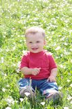 Smiling baby outdoors against flowers. Smiling baby age of 10 months outdoors against flowers Royalty Free Stock Photo