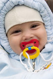 Smiling baby with pacifier. Smiling baby boy in blue snowsuit with pacifier Royalty Free Stock Photography