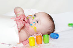 Smiling baby with paper and finger-type paints Stock Photography