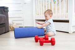 Smiling baby playing on floor with fitness mat and dumbbells. Co Stock Photos