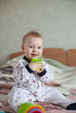 Smiling Baby playing with Multicolored shape sorter toy. On the bed royalty free stock images
