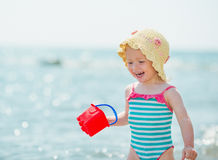 Smiling baby playing with pail on seashore Stock Images