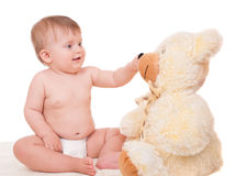 Smiling baby playing with teddy bear Stock Image