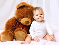 Smiling baby playing with teddy bear Royalty Free Stock Images