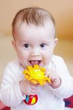 Smiling baby plays rattle Stock Photos