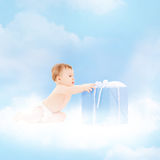 Smiling baby with present on the cloud. Childhood and present concept - smiling baby sitting on the cloud with big gift box stock photo
