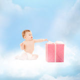 Smiling baby with present on the cloud. Childhood and present concept - smiling baby sitting on the cloud with big gift box royalty free stock images