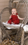 Smiling Baby in Red Overalls. A laughing baby sits in a rustic chair, wearing red overalls. Autumn leaves add a nice autumn feel Royalty Free Stock Images