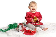 Smiling baby in red velvet dress and holiday gifts Stock Photos