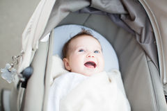 Smiling baby relaxing in a stroller. Smiling little baby relaxing in a stroller Stock Photography