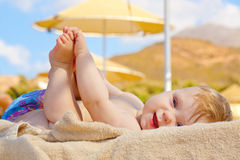 Smiling baby resting on the beach sunbed. Stock Photos