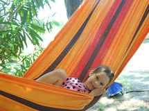 Smiling baby rests in a hammock of the resort during the summer Stock Photos