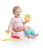 Smiling baby sitting on chamber pot. With toilet paper roll royalty free stock images