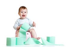 Smiling baby sitting on chamber pot with toilet paper roll. Baby girl sitting on chamber pot with toilet paper roll stock photo