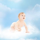 Smiling baby sitting on the cloud Stock Photos