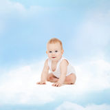 Smiling baby sitting on the cloud Royalty Free Stock Photo