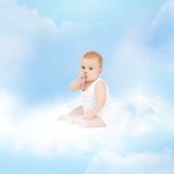 Smiling baby sitting on the cloud Stock Images
