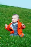 Smiling baby sitting on grass. Smiling baby sitting on green grass on blue sky background royalty free stock photography