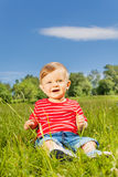 Smiling baby sitting on the green grass alone Royalty Free Stock Photo
