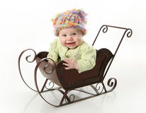 Smiling baby sitting in a sled Royalty Free Stock Photography