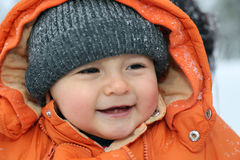 Smiling baby with snow in winter Royalty Free Stock Photos