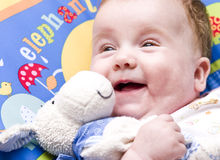 Smiling baby with soft toy Royalty Free Stock Photos